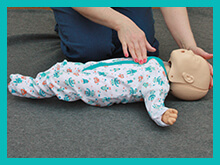 baby resus doll having cardiac massage carried out