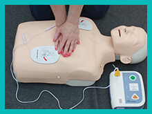 Resus dummy with defibrillator being demonstrated