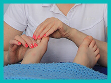 Karen carrying out a reflexology therapy on a clients feet