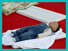 Baby massage doll lying on mat ready for a baby massage session
